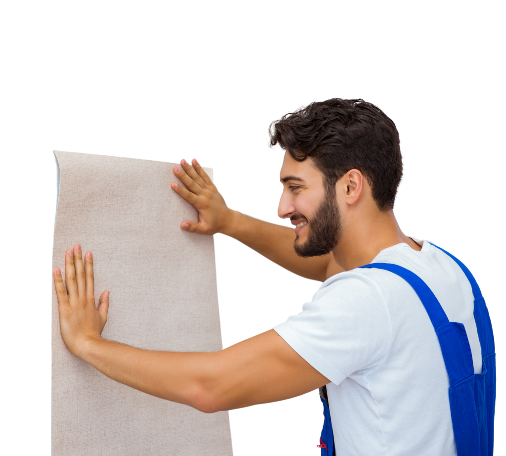 A young man with a brown beard smiles as he hangs a piece of wallpaper on the wall for a Raleigh Wallpaper installation project