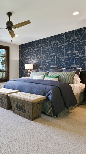 A hotel bed with blue blankets sits in front of a wall with navy blue nautical-themed wallpaper that Raleigh Wallpaper did wallpaper installation for