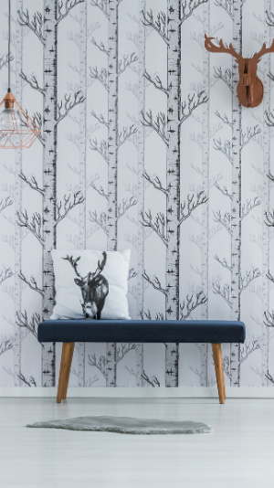 A bench with a pillow printed with a deer head sits in front of a wall with tall birtch tree wallpaper. This wallpaper has been repaired by Raleigh Wallpaper