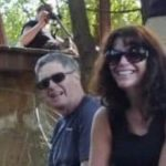 A couple wearing sunglesses sit in a wooded area and grin at the camera